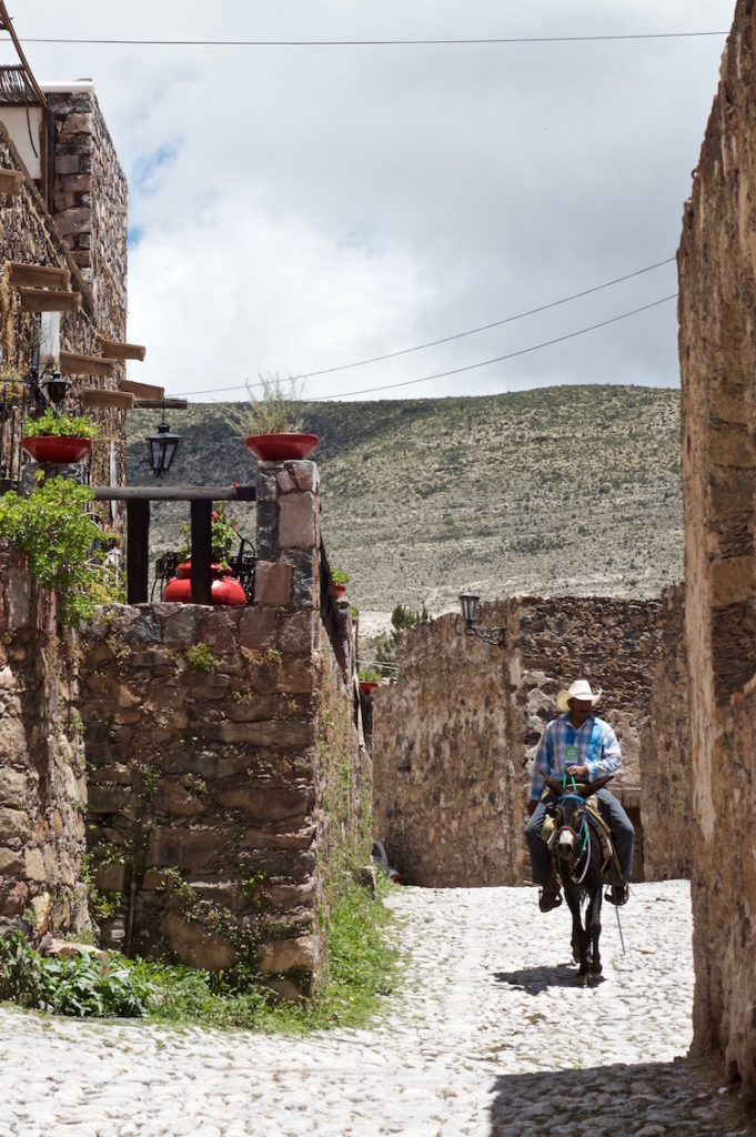 Cowboy on his mule riding through the old village of Real de Catorce, Mexico