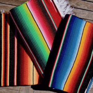 Colourful Mexican blankets folded and on a pile on a wooden table