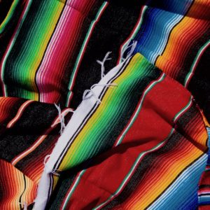 Colourful Mexican blankets unfolded on a pile with blue, orange, green, black, pink, red and yellow stripes