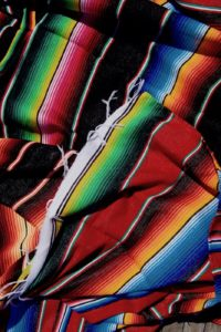 Colourful Mexican blankets unfolded on a pile with blue, orange, green, black, pink and yellow stripes