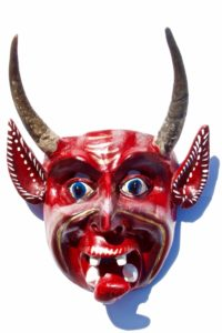 Wooden devils mask hand carved out of wood and painted in a bright red color