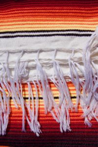 White braids on an orange Mexican blanket with black, yellow and red stripes
