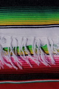 White braids on a red Mexican blanket with green and pink stripes