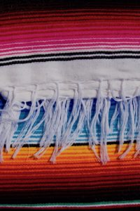 White braids on a black Mexican blanket with pink and orange stripes