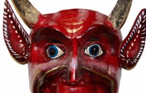 Close up of the face of a red devil mask with blue eyes and goat horns