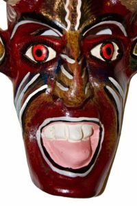 Close up of a Mexican devil mask with red eyes and a golden painting