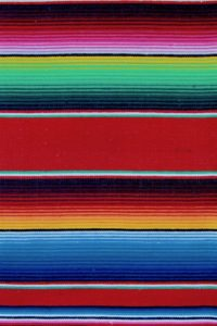 All the colours on the red Mexican blanket like blue, red, white, pink, black, yellow, green