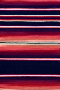 Orange Mexican blanket with bright orange and red pattern on black and thin red, white stripes running through