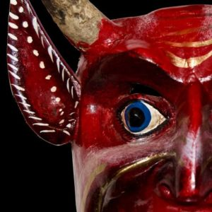 Close up of the blue eye of a Mexican red devils mask in front of a black background